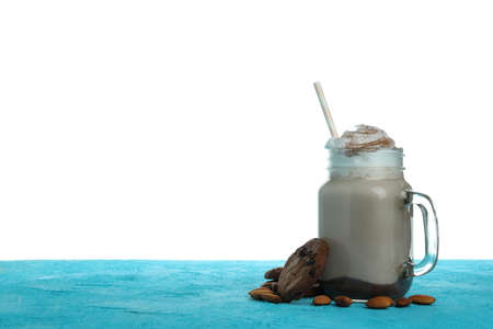 Chocolate milkshake, cookies and almond on blue textured table isolated on white background