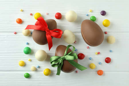 Easter chocolate eggs and candies on white wooden table