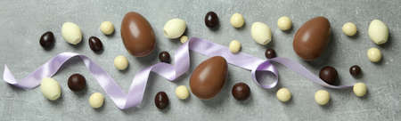 Easter chocolate eggs and candies on gray background
