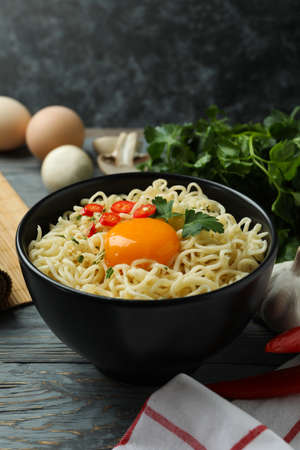 Bowl of cooked noodles and ingredients on wooden background