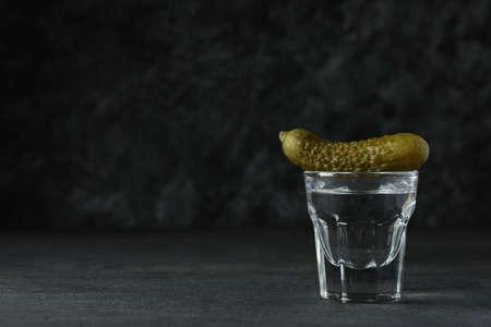 Shot of vodka and pickle on dark background 免版税图像