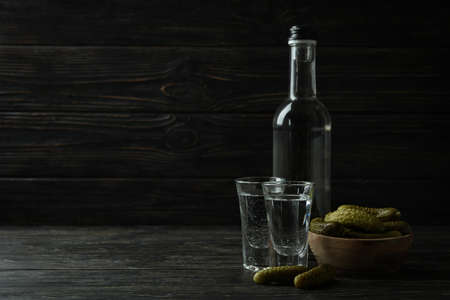 Bottle and shots of vodka, and pickles on wooden background 免版税图像