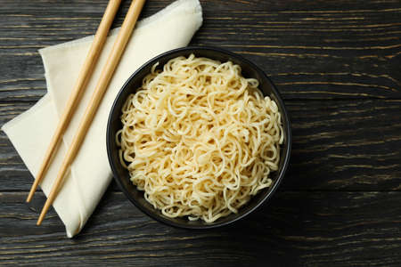 Napkin with chopsticks and bowl with noodles on wooden background