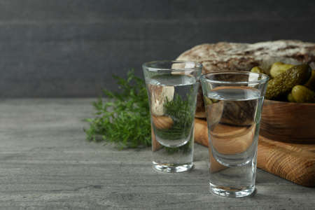 Shots of vodka, pickles, bread and dill on gray table