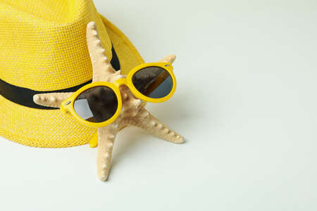 Hat, seastar, and sunglasses on white background