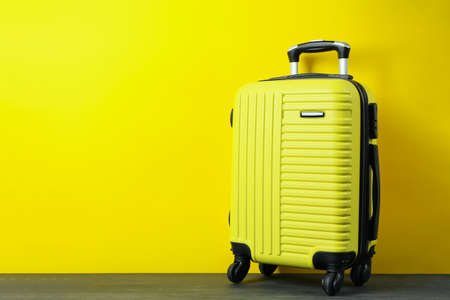 Travel bag on yellow background, space for text