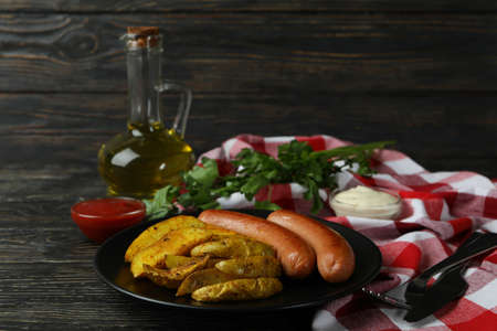 Concept of tasty meal with potato wedges on wooden background 免版税图像
