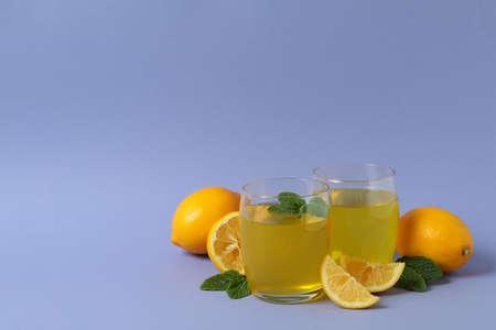 Glasses of lemon jelly, lemon slices and mint on violet background
