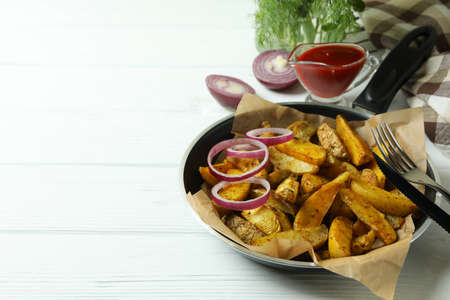 Concept of tasty meal with pan of tasty potato wedges