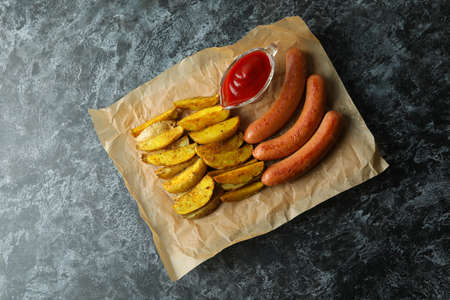 Paper with fried potato, sauce and sausages on black smokey background 免版税图像