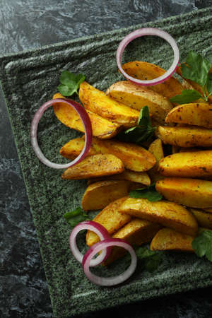 Plate with potato wedges, parsley and onion on black smokey background