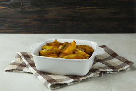 Bowl with fried potato on kitchen towel, on white textured table 免版税图像