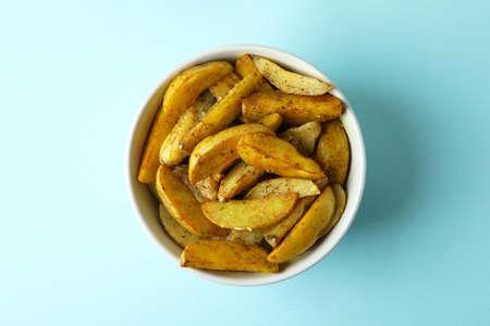 Bowl of potato wedges on blue background
