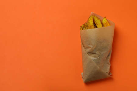 Baking paper with potato wedges on orange background 免版税图像