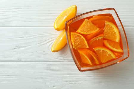 Bowl of orange jelly with orange slices on white wooden background