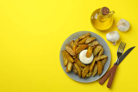 Concept of tasty eating with baked potato on yellow background