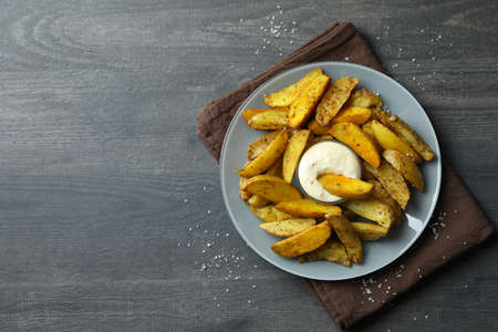 Plate with potato wedges and sauce on dark textured background 免版税图像