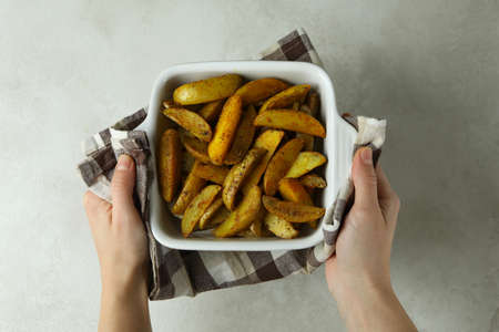 Female hands hold bowl of potato wedges