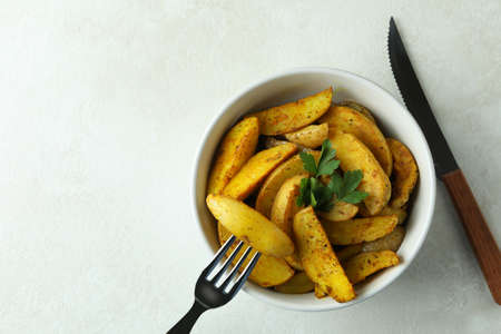 Bowl of potato wedges and cutlery on white textured background 免版税图像