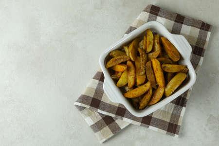 Bowl with fried potato on kitchen towel, on white textured background 免版税图像