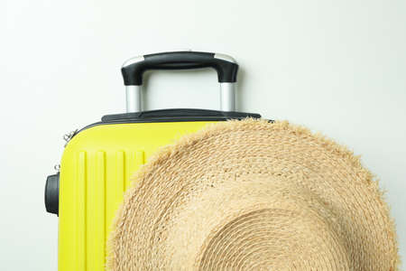 Straw hat and travel bag on white background