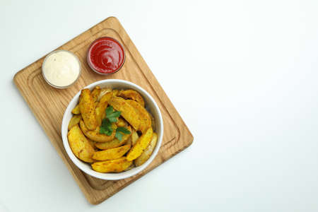 Board with bowl of potato wedges and sauces on white background