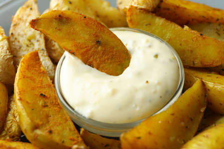 Tasty potato wedges and bowl of sauce, close up