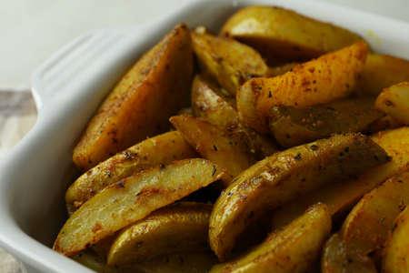 Bowl of tasty potato wedges, close up