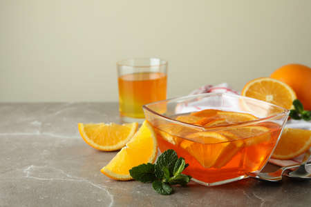 Concept of dessert with bowl of orange jelly with orange slices on gray table