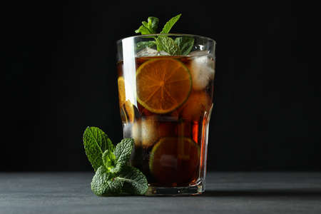 Glass of Cuba Libre and mint against dark background