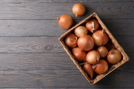 Basket with fresh onion on wooden background Standard-Bild