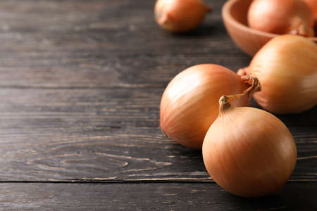 Ripe fresh onion on wooden background, space for text Standard-Bild