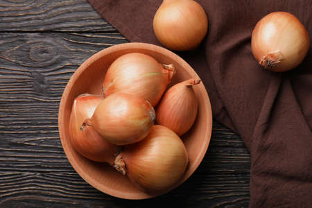 Bowl with fresh onion and kitchen towel on wooden background Standard-Bild
