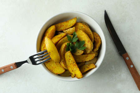 Bowl of potato wedges and cutlery on white textured background Standard-Bild