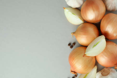 Fresh onion and peppercorns on light gray background