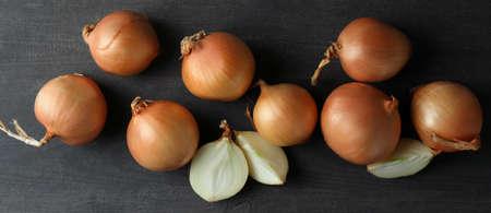 Fresh ripe onion on black wooden table