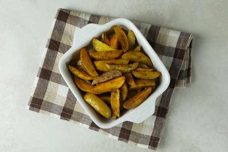 Bowl with fried potato on kitchen towel, on white textured background Standard-Bild