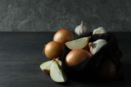 Bag with onion and garlic on black wooden table