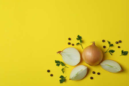 Onion, peppercorns and parsley on yellow background