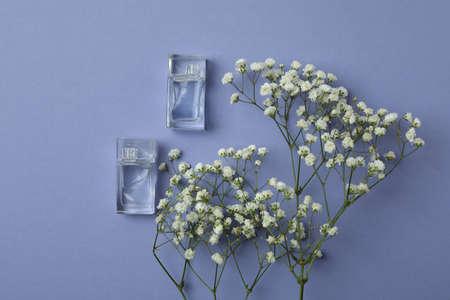 Perfume mini bottles and flowers on violet background Standard-Bild