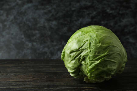 Fresh green cabbage on wooden table, space for text