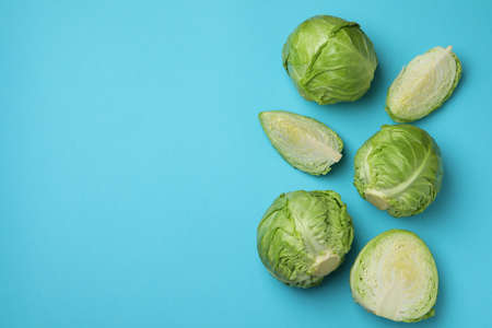 Fresh green cabbage on blue background, space for text