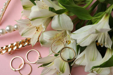 Jewelry and flowers on pink background, close up