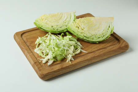 Board with fresh green cabbage on white background
