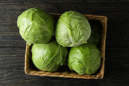 Basket with fresh cabbage on wooden table Standard-Bild