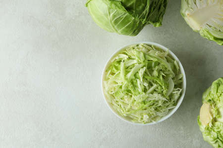 Bowl with sliced cabbage and fresh cabbage on white textured table Standard-Bild