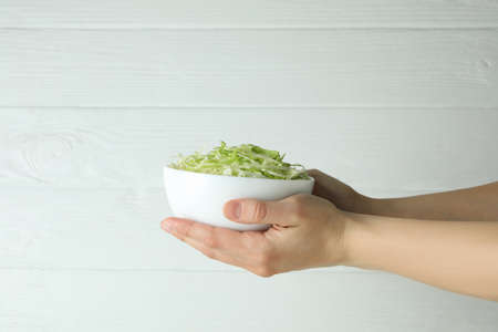 Female hands hold bowl with sliced cabbage on white wooden background Standard-Bild