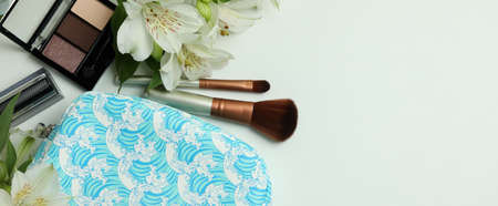 Cosmetic bag, cosmetics and alstroemeria on white background