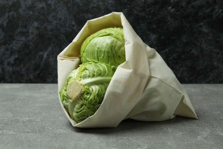 Bag with fresh green cabbage on gray table