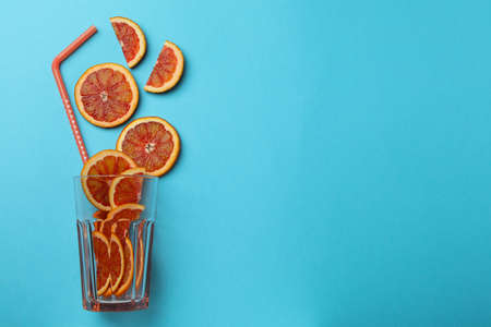 Glass with red orange slices and straw on blue background Standard-Bild - 167152766